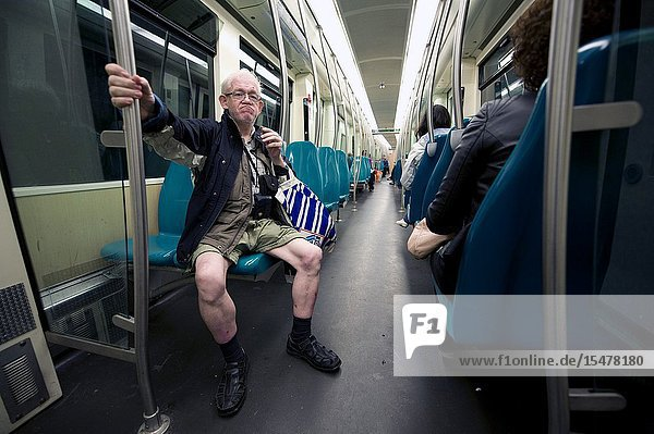 Rotterdam  Netherlands. Senior adult male in shorts  with skinny legs commuting by subway from Central Station towards his neighborhood.