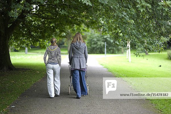 Rotterdam  Netherlands. A new mother with her baby in a carriage walking and strolling Kralingen Forrest (Kralingse Bos) with a female friend while they are having a conversation.