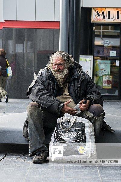 The Hague  Netherlands. Neglected  alcoholic and homeles man sitting his dirty self down inside a down town shopping street.