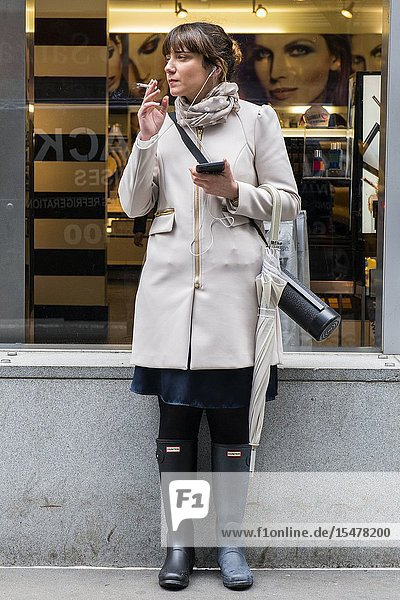 New York City  New York  USA. Young  attractive and fashionable woman smoking her hourly cigarette just outside the shop and store she is working. Smoking tobacco products inside workplaces is nog longer allowed  toe prevent other from inhaling unhealthy chemicals.