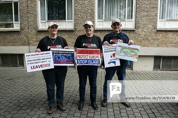 Breda  Netherlands. Group of Pegida supporters with sign protesting during a local rally and demonstration. Pegida is a patriotic political organization opposing to immigration of Islamic & Muslim people into the Christian  Western-European Culture.