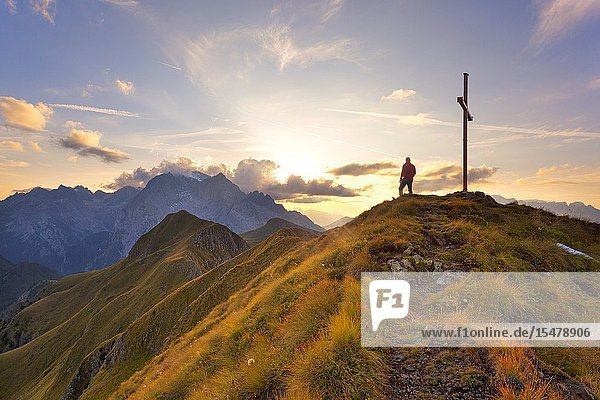A hiker admires the sunset on Marmolada group from the grassy summit of Migogn Mount  Dolomites  Marmolada group  Rocca Pietore  Belluno province  Veneto  Italy.