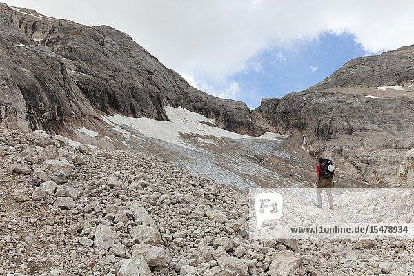 A hiker looks the Vernel Glacier  Marmolada group  Dolomites  Canazei  Trento province  Trentino-Alto Adige  Italy.