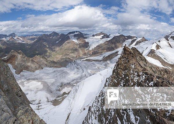 Panoramic of hikers on rocks looking at Forni glacier from Dosegù  Gavia Pass  Valfurva  Valtellina  Lombardy  Italy.
