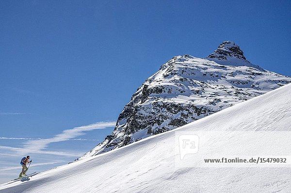 Ski mountaineer on steep snowy slope towards Pizzaccio  Valchiavenna  Valtellina  Sondrio province  Lombardy  Italy.