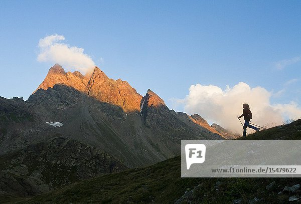 Europe  Italy  Lombardy  Sondrio. Trekker's silhouette at sunset in the mountains of Viola valley  Valtellina.