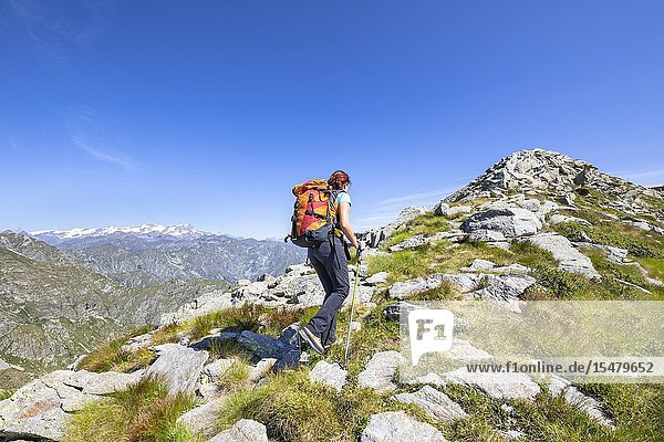 A girl is walking towards the Monte Camino on the mountains of Biella above Oropa: the Matterhorn and the Monte Rosa in the left. (Oropa Valley  Biella  Biella province  Piedmont  Italy  Europe).
