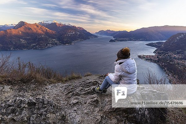 A girl staring at the view of the center and the two branches of Lake Como during a windy winter sunset from Breglia. Plesio  Como Lake  Lombardy  Italy.