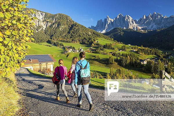 People walking towards the village of St. Magdalena  Funes Valley  province of Bolzano  South Tyrol  Italy.