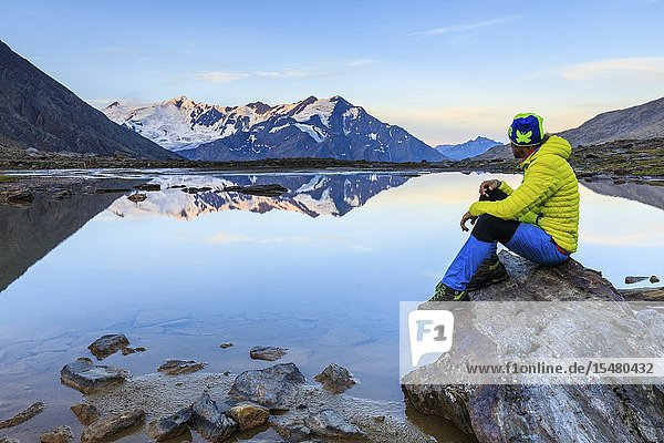 Hiker looks at Pizzo Tresero and Punta San Matteo from Cedec lake  Stelvio National Park  Valtellina  Sondrio province  Lombardy  Italy.