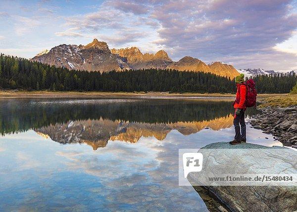 Hiker admiring sunrise from the shore of Lake Palù  Malenco Valley  Valtellina  Sondrio province  Lombardy  Italy.