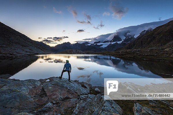 Hiker admiring Piz Argent and Zupò from lake Confinale  Valmalenco  Valtellina  Sondrio province  Lombardy  Italy.