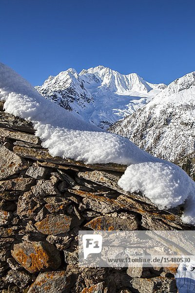 Stone hut covered with snow with Monte Disgrazia on background  Alpe dell'Oro  Valmalenco  Valtellina  Lombardy  Italy.