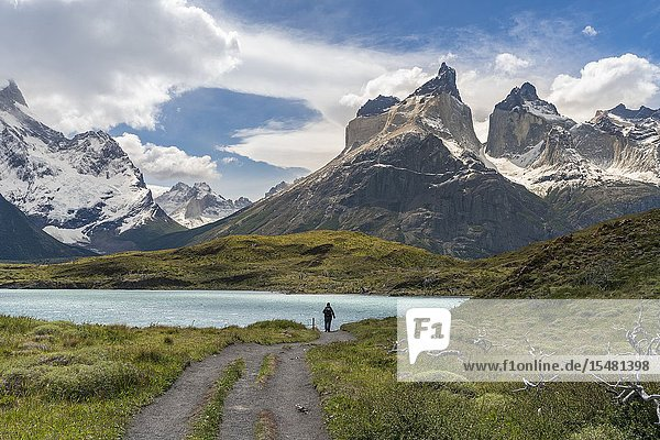 Woman walking on the footpath towards Mirador Cuernos  with Nordenskjold Lake and Paine Horns in the background  in summer. Torres del Paine National Park  Ultima Esperanza province  Magallanes region  Chile.