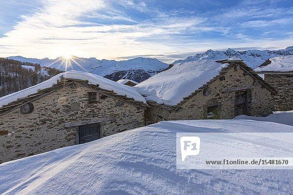 Sunburst on the snowy huts  Alpe Groppera  Madesimo  Valchiavenna  Valtellina  Sondrio province  Lombardy  Italy.