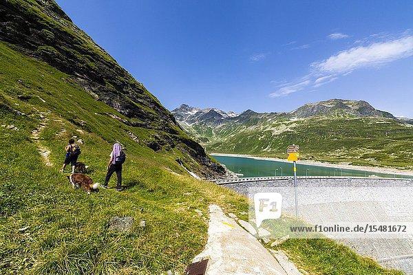 Hikers with dogs on path at dam of lake Montespluga  Chiavenna Valley  Sondrio province  Valtellina  Lombardy  Italy.