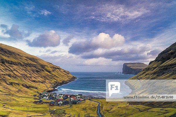 Clouds at dawn over the ocean and coastal village of Tjornuvik  Streymoy island  Faroe Islands  Denmark.