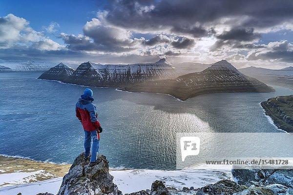 Hiker on rocks admiring the rays of sun over Funningur fjord  Eysturoy island  Faroe Islands  Denmark.