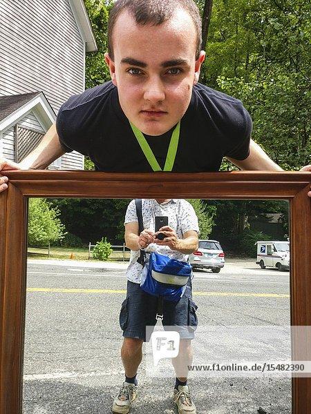 Cornwall  Connectcut  USA A teenage boy carries a mirror to an antique shop.
