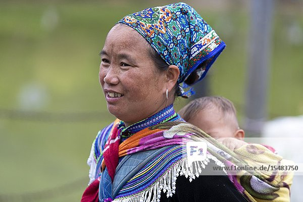 Flowers Hmong (hill tribe)  woman carrying his son on her back  at the sunday market  Bac Ha  Lao Cai Province  Vietnam  Asia.
