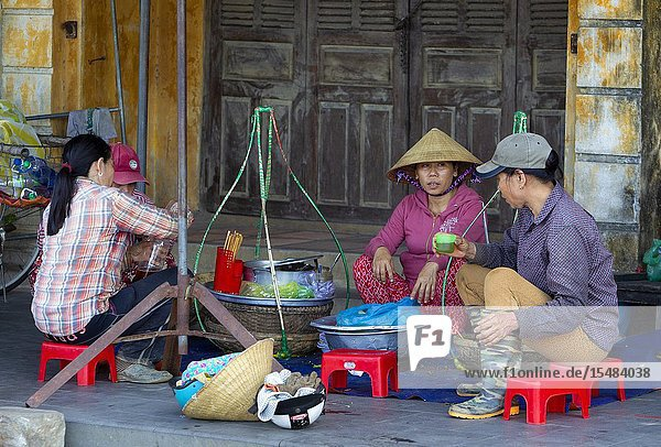 Woman selling food and drinks in the street  and people eating around her  Hoi An Old Town  Quang Nam province  Vietnam.