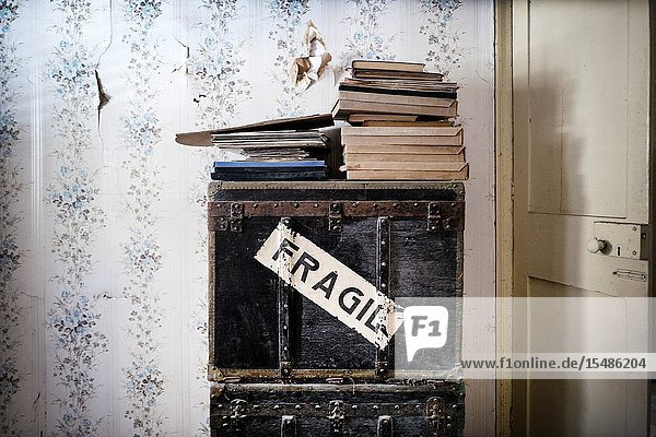 Piled up boxes and books inside a room and Fragile written on one of the boxes in a house. Mahon  Menorca  Balearic Islands  Spain