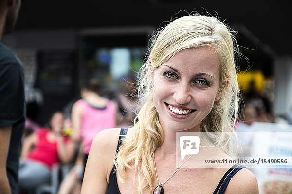 Tilburg  Netherlands. Young blonde and smiling woman visiting the annual fair's Pink Monday.