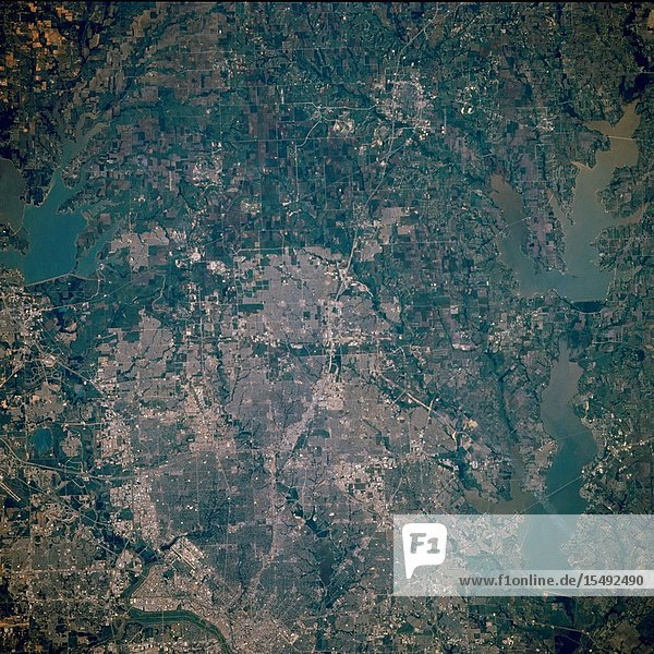 The northern two-thirds of Dallas and such peripheral cities as Richardson  Plano  Allen  and McKinney to the north are featured in this near-vertical photograph of a region experiencing tremendous population growth. Visible are the central business district of downtown Dallas (west of center)  the runways of Dallas Love Field (northwest of downtown)  and north-south U.S. Highway 75  the Central Expressway. Three large reservoirs and their respective dams are apparent-Garza Little Elm Reservoir northwest of Dallas  Lavon Reservoir to the northeast  and Lake Ray Hubbard to the east. Visible are White Rock Creek  a tributary of the Trinity River  meandering southward through central Dallas  the street pattern of most of the surrounding cities  and cultivated (angular) agricultural fields north of the cities.