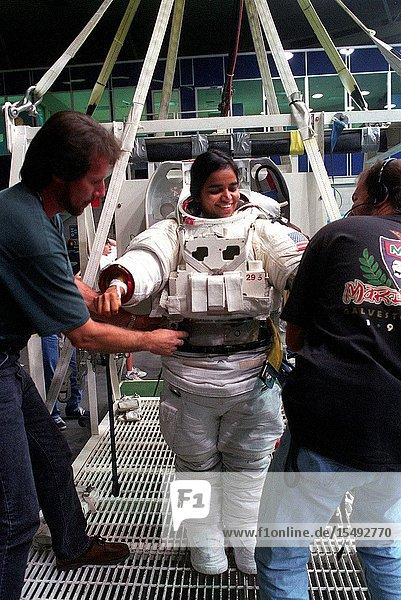 Astronaut Kalpana Chawla  STS-87 mission specialist  receives assistance in donning a training version of the Extravehicular Mobility Unit (EMU) space suit prior to an underwater training exercise. Chawla is not one of the STS-87 crewmembers assigned to a scheduled spacewalk.