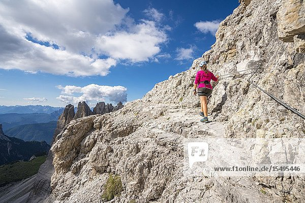 Young woman walking on the via ferrata that leads to the summit of Mount Paterno  in summer. Sesto Dolomites  Trentino Alto Adige  Italy.