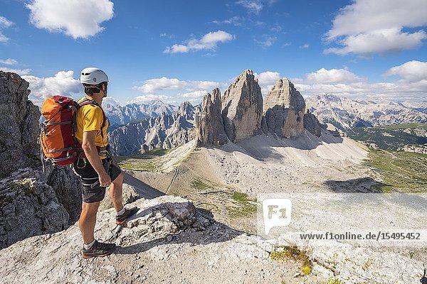 Man admiring the landscape around the Three Peaks of Lavaredo from the summit of Mount Paterno  in summer. Sesto Dolomites  Trentino Alto Adige  Italy.