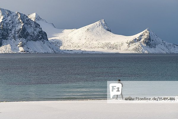 Man standing taking pictures of the mountains from Haukland Beach in winter. Leknes,  Nordland county,  Northern Norway,  Norway.