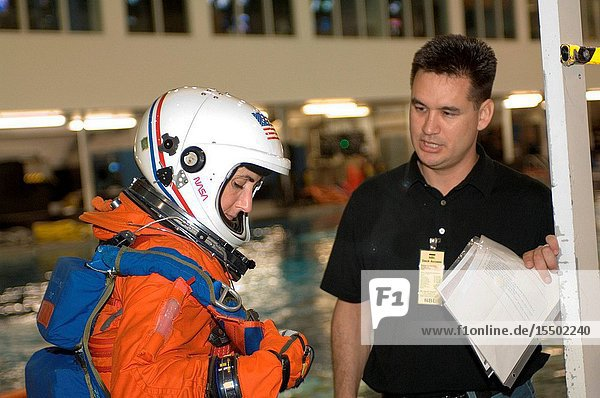 Attired in a training version of the shuttle launch and entry suit  astronaut Nicole Stott  Expedition 2021 flight engineer  prepares for a water survival training session in the Neutral Buoyancy Laboratory (NBL) near NASA's Johnson Space Center. United Space Alliance (USA) crew trainer Adam Flagan assisted Stott.
