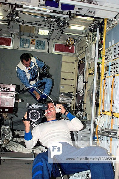 Cosmonaut Vladimir Dezhurov  Expedition Three flight engineer  operates a video camera in the Zvezda Service Module. In the background  cosmonaut Mikhail Tyurin  flight engineer  is visible with a photographic camera. Tyurin and Dezhurov represent Rosaviakosmos.