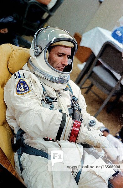 Astronaut Richard F. Gordon Jr.  pilot of the Gemini-11 spaceflight  reclines on a couch as he adjusts his spacesuit in the Launch Complex 16 suiting trailer during the Gemini-11 prelaunch countdown. He is already wearing the full suit and helmet.