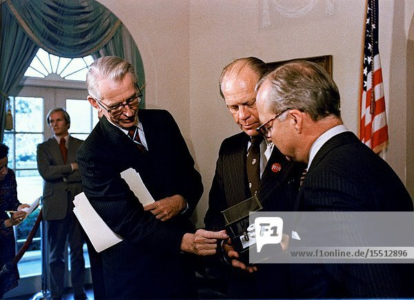 Dr. James C. Fletcher  left  NASA Administrator  explains the formation of the indium-antimonide crystal  manufactured in space  to President Gerald R. Ford at the White House. Standing at right is Harold Johnson  Chairman of the Massachusetts Institute of Technology. The segment of indium-antimonide is cut from a cylindrical single crystal that was partially melted and resolidified aboard the Skylab space station on Jan. 6  1974  during the third and final manned flight. This segment is approximately one by one centimeters and about three millimeters thick. The sequence of heating and cooling was started and supervised by the members of the third Skylab crew  astronauts Gerald P. Carr  Edward G. Gibson and William R. Pogue. The crystal forming was accomplished in a special multipurpose furnace  known as the Materials Processing Facility (Skylab Technology Experiment M512).