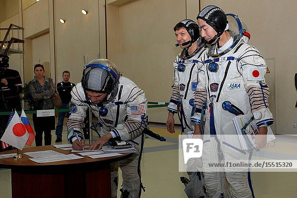 At the Gagarin Cosmonaut Training Center in Star City  Russia  Expedition 4243 backup crewmember Kjell Lindgren of NASA signs in for the first of two days of qualification exams October 30 as his crewmates  Oleg Kononenko of Roscosmos (center) and Kimiya Yui of the Japan Aerospace Exploration Agency look on. They are the backups to the prime crew Terry Virts of NASA  Anton Shkaplerov of Roscosmos and Samantha Cristoforetti of the European Space Agency --- who are in the final stages of training for launch November 24  Kazakh time  in the Soyuz TMA-15M spacecraft to begin a five and a half month mission on the International Space Station.