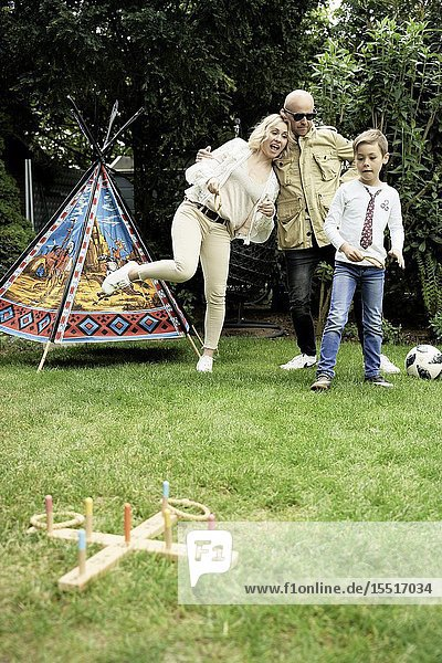 Family playing game in garden.