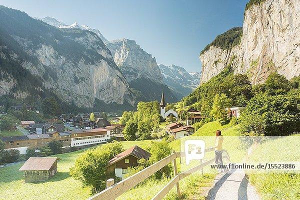 A young woman admiring the village of Lauterbrunnen Interlaken-Oberhasli administrative district  canton of Bern Bernese Oberland  Switzerland.