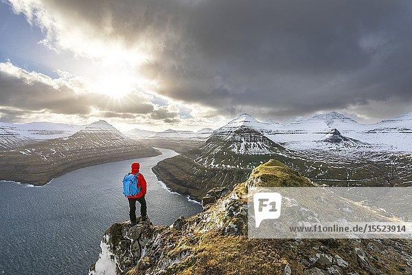 Hiker standing on peak over Funningur fjord (Eysturoy island  Faroe Islands  Denmark) (MR).