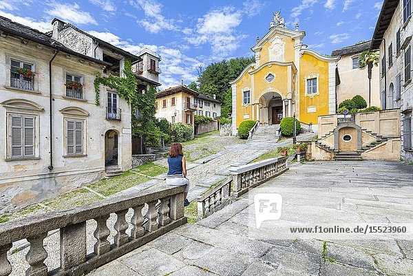 A tourist is looking the church of Santa Maria Assunta (Orta San Giulio  Lake Orta  Novara province  Piedmont  Italy  Europe) (MR).