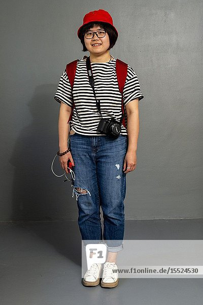 Tilburg  Netherlands. Young  female Chinese tourist with camera roaming the city for images and memories. Studio Portrait.