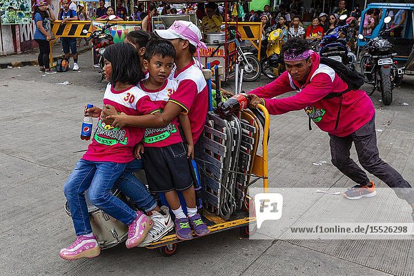 A Young Man Pushes A Group Of Children Around On A Trolley  The Ati-Atihan Festival  Kalibo  Panay Island  Aklan Province  Western Visayas  The Philippines.