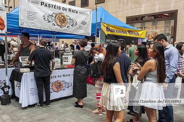 Tourists and office workers line up at Pasteis De Nata in The Outpost of the Queens Night Market  located in Rockefeller Plaza in New York on Tuesday  July 30  2019. The marketplace features ethnic and artisanal foods by small entrepreneurs all of whom are regulars at the Queens Night Market. Nine vendors will encamp in the plaza Monday through Thursday for three weeks. (© Richard B. Levine).