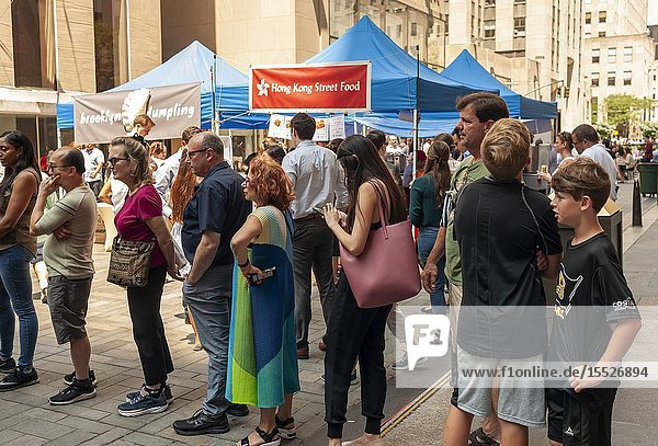 Tourists and office workers flock to The Outpost of the Queens Night Market  located in Rockefeller Plaza in New York on Tuesday  July 30  2019. The marketplace features ethnic and artisanal foods by small entrepreneurs all of whom are regulars at the Queens Night Market. Nine vendors will encamp in the plaza Monday through Thursday for three weeks. (© Richard B. Levine).