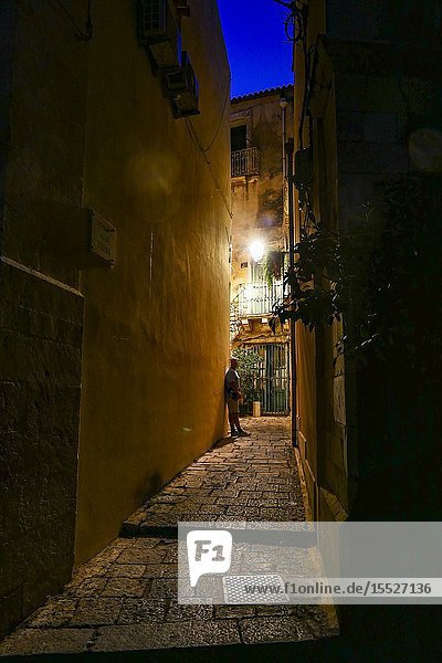 Syracuse  Sicily  Italy A pedestrian on the back streets of Ortygia island at dawn.