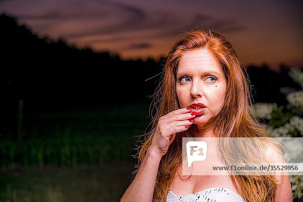 40 year old redheaded woman in a white dress in a garden setting in the spring.