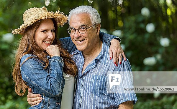 A 40 Year old readheaded woman and a 66 year old man smiling at the camera  outdoors.