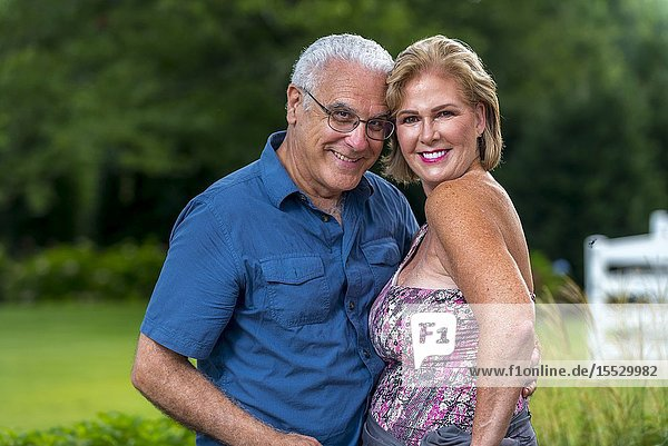 A happy 60 Year old blond woman and a 66 year old man smiling at the camera  outdoors.