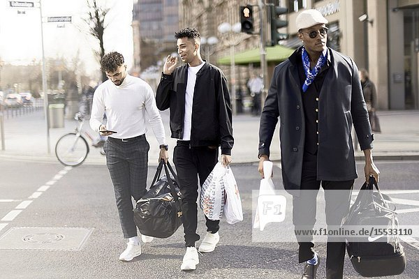 Three men coming from shopping tour in city Frankfurt  Germany